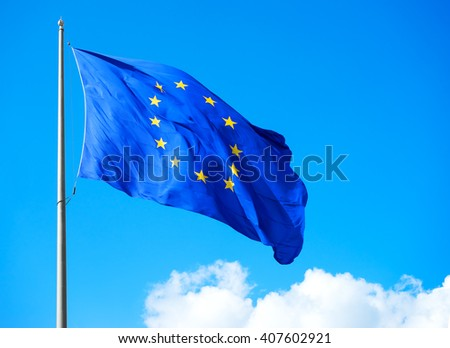 Bright EU flag against the blue sky closeup. EU symbol