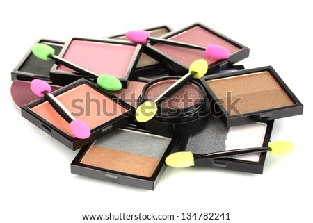 Bright eye shadows and sponge brushes for foundation isolated on white