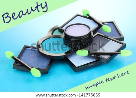 Bright eye shadows and sponge brushes for foundation on blue background