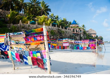 Bright fabric for sale on a white sand beach in a beautiful holiday location - stock photo