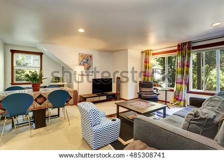 Bright Family room interior connected with dining area. Comfortable gray loveseat, leather chair and colorful curtains. Northwest, USA