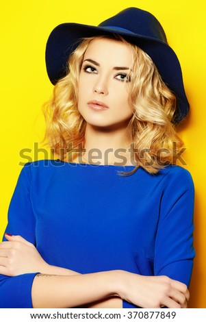 Bright fashion concept.  Beautiful girl with curly blonde hair wearing blue dress posing over yellow background.  - stock photo