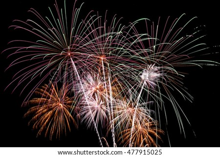 Bright festive background with beautiful colored fireworks, salute on the background of the black sky