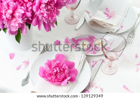 Bright festive table setting with pink peonies, candles and vintage cutlery