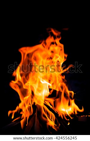 Bright flame of bonfire. Defocused. Toned. - stock photo