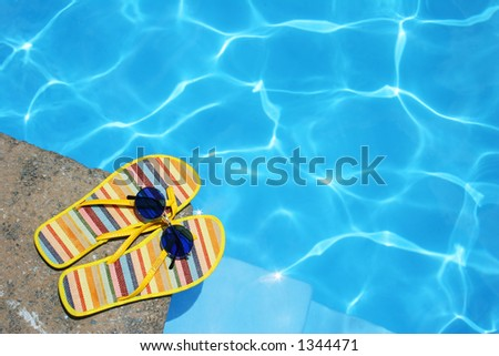 Bright Flip-flops and sunglasses by swimming pool - stock photo