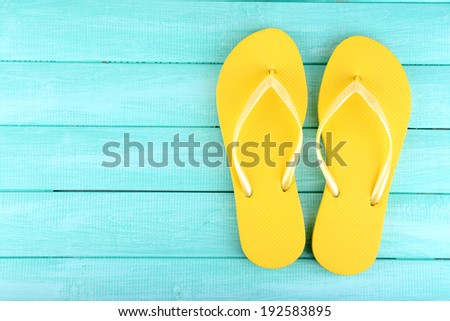 Bright flip-flops on color wooden background - stock photo