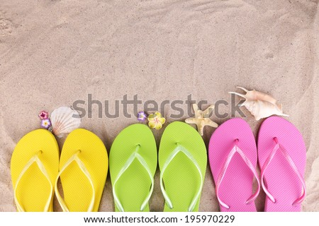 Bright flip-flops on sand, close up - stock photo