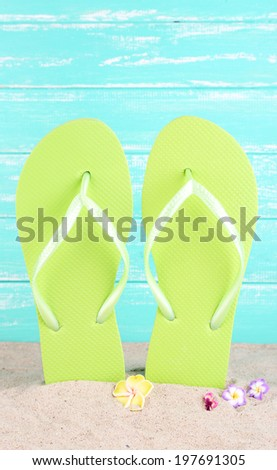 Bright flip-flops on sand, on wooden background