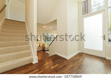 Bright Foyer / Entryway with spacious stairway in modern townhouse - stock photo