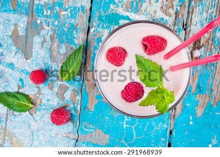 Bright fresh delicious milkshake with fresh ripe raspberries and a sprig of fresh mint, two cocktail stick, top view, close up - stock photo