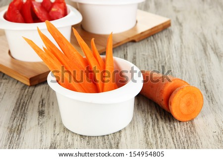 Bright fresh vegetables cut up slices in bowls on wooden table close-up