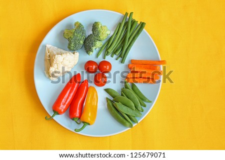 Bright, fresh vegetables on the blue plate and yellow background - stock photo