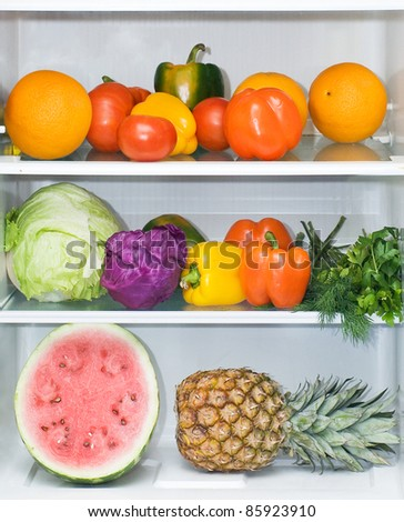Bright fruit and vegetables are on the shelves in the refrigerator. - stock photo