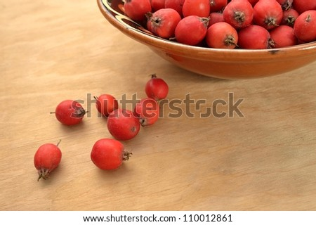 Bright fruit of the hawthorn in clay bowl on wooden table - stock photo