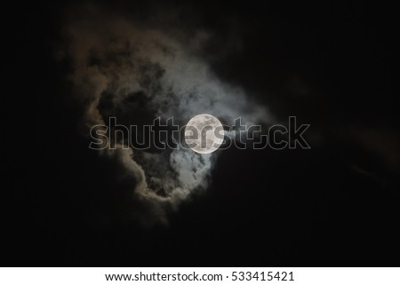 Bright full moon on cloudy scene of night sky. Elements of this image furnished by NASA.