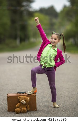 Bright funny little girl on the road with a suitcase and a teddy bear. - stock photo