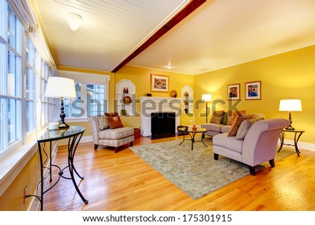 Bright furnished living room with designed ceiling and yellow wall - stock photo