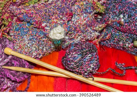 Bright gaudy natural fiber wools and knitting needles - stock photo