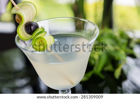 bright glasses with cold alcoholic cocktail on a table in a restaurant with creative decoration. soft focus - stock photo