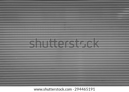 Bright gray metal sliding door with key hole, taken on a cloudy day. - stock photo