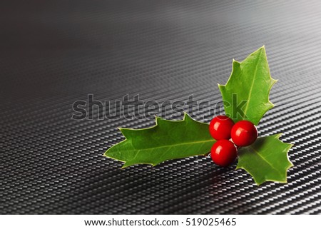 Bright green Christmas holly with red berries on dark carbon fiber background