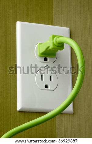 Bright green electrical cord is plugged into white outlet - stock photo