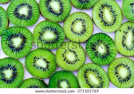 Bright green slices of kiwi fruit as a background. - stock photo