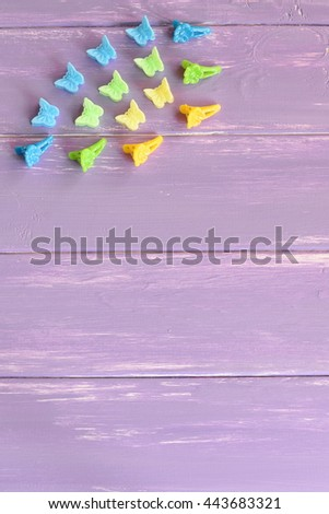 Bright hair clips with flowers and butterflies. Kit of colorful hair clips for girls on lilac wooden background with copy space for text. Vertical photo. Top view - stock photo