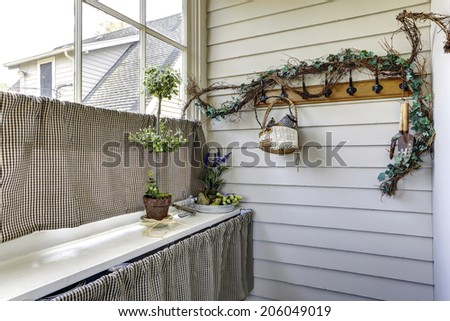 Bright hallway corner view. Decorated window with pleated curtains and flowers blend perfectly with dry branch over the hanger on the wall