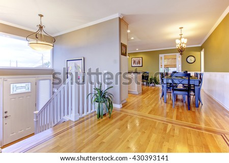 Bright hallway with polished hardwood floor. Open wall design with dining room - stock photo
