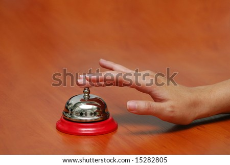 bright hand-bell on a table, hand press button