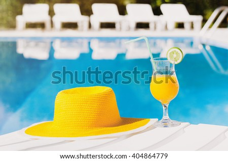 Bright hat with cocktail over a swimming pool, vacations concept - stock photo