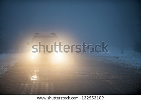 Bright headlights of a car driving on foggy winter road - stock photo