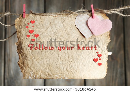 Bright hearts and card hanging on rope on wooden background - stock photo