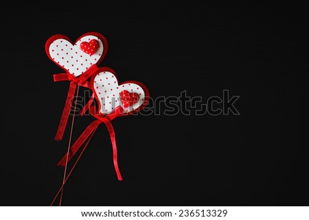 bright holiday valentine on a stick on a black wooden background. valentine's day. festivals and events. copy space for you text