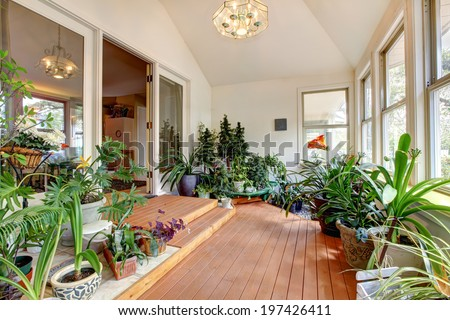 Bright home greenhouse with high vaulted ceiling and hardwood floor. Room full of plants and blooming flowers - stock photo
