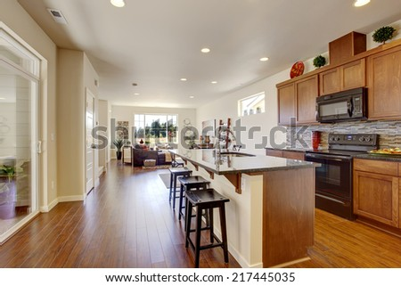 Bright house interior. Kitchen room with kitchen island and tile back splash trim