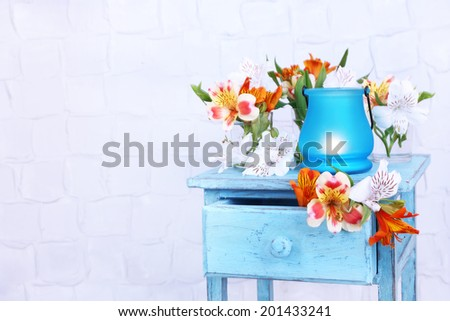 Bright icon-lamp with flowers on wooden stand on light background - stock photo