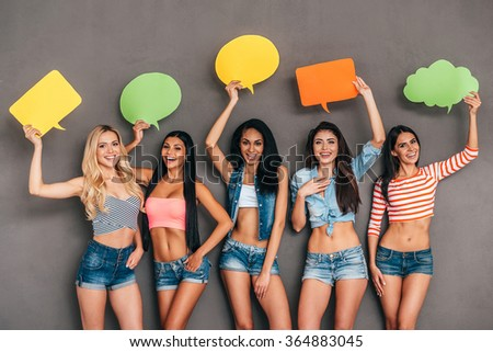 Bright ideas. Five beautiful young women holding speech bubbles with copy space over their head while posing against grey background - stock photo