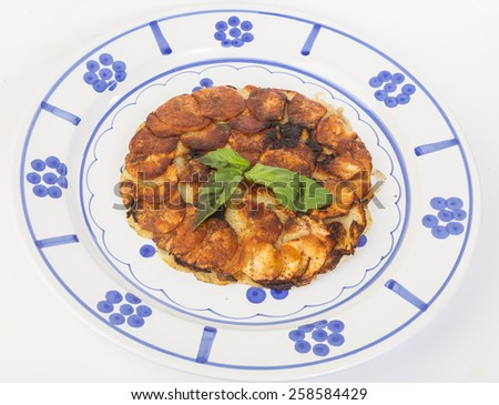 Bright image of golden brown potato and onion Frittata on white platter decorated with blue pattern and grapes to represent the Italian origin.  White background. - stock photo