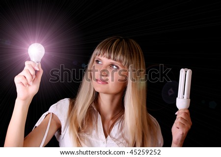 bright incandescent bulb in young woman hands on black background - stock photo
