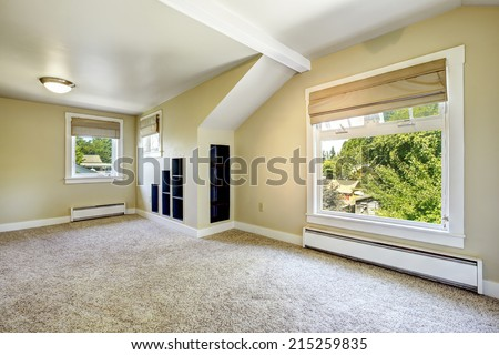 Bright ivory room with vaulted ceiling, built-in shelves and carpet floor. Empty house interior