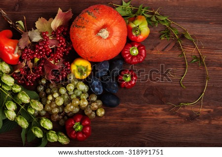 Bright juicy autumn background with orange pumpkin, grapes, hops, pepper and snowball on a brown wooden background. Place for writing text. Vegan concept