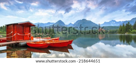 Bright juicy red boats, landing near the bank of the clear blue lake, reflected in the water, with the romantic view on the big green Tatra Mountains - stock photo