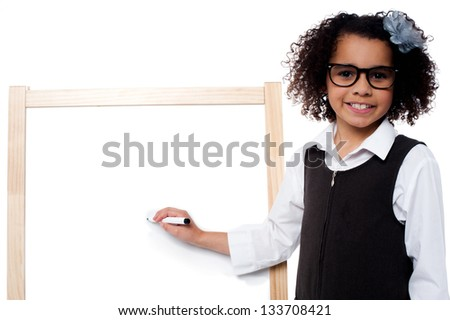 Bright kid wearing spectacles and writing on whiteboard with black marker pen. - stock photo