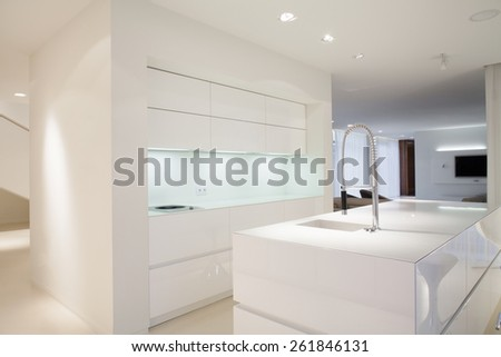 Bright kitchen interior with simple white cupboards - stock photo