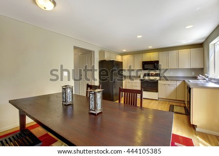 Bright kitchen room with beige cabinets and black appliances.