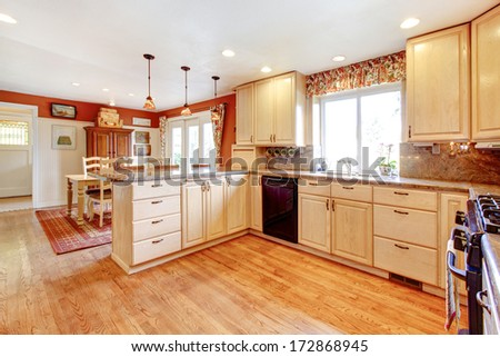 Bright kitchen room with enclosed dining area. Light tones furniture and contrast red color walls - stock photo