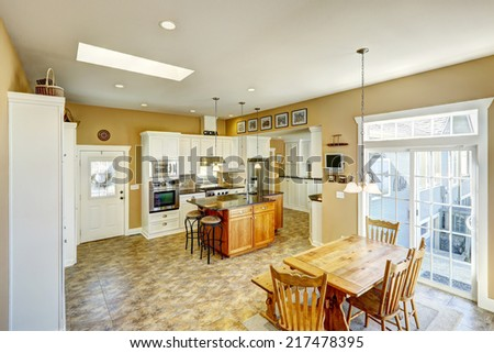Bright kitchen room with kitchen island, white cabinets and rustic dining table set